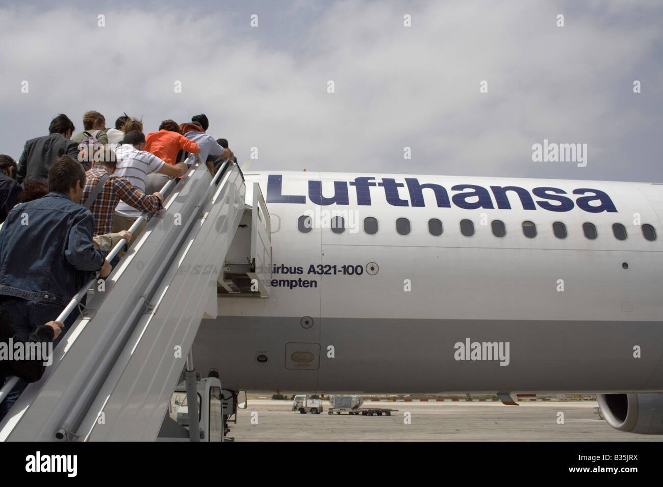 Commercial air travel. Passengers boarding a Lufthansa Airbus A321 airliner by means of a mobile staircase or ramp - Stock Image