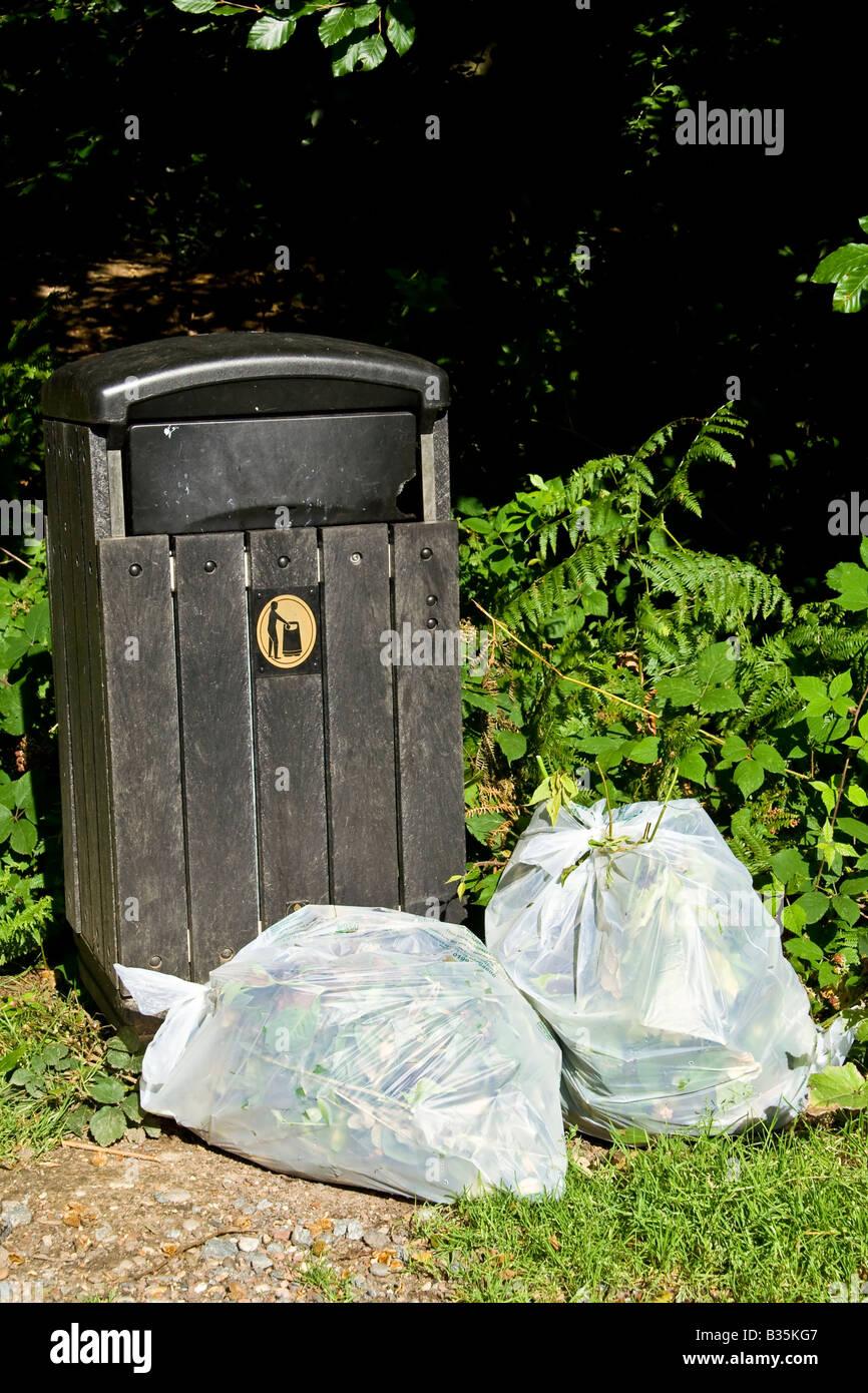 Rubbish bags by a litter bin, UK. - Stock Image