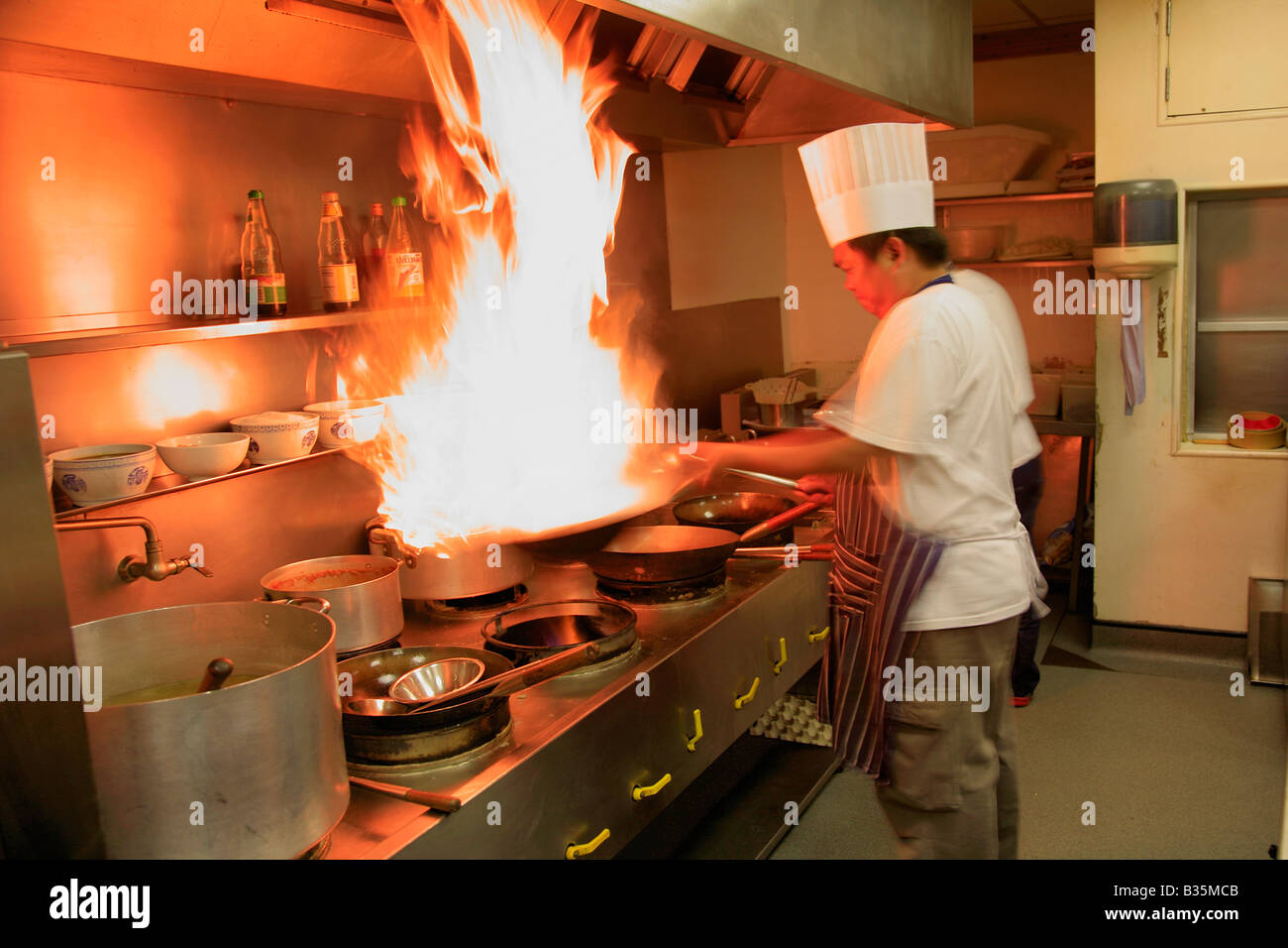 Male thai chef cooking with flaming wok in a restaurant for Fresh chef kitchen