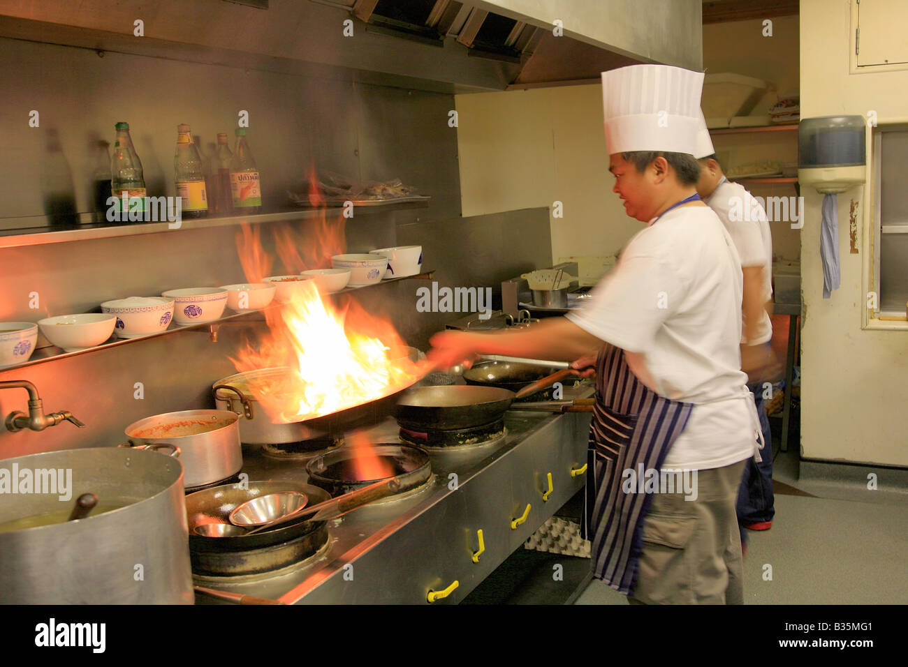 Male Thai Chef Cooking With Flaming Wok In A Restaurant Kitchen, Oriental  Cuisine   Stock