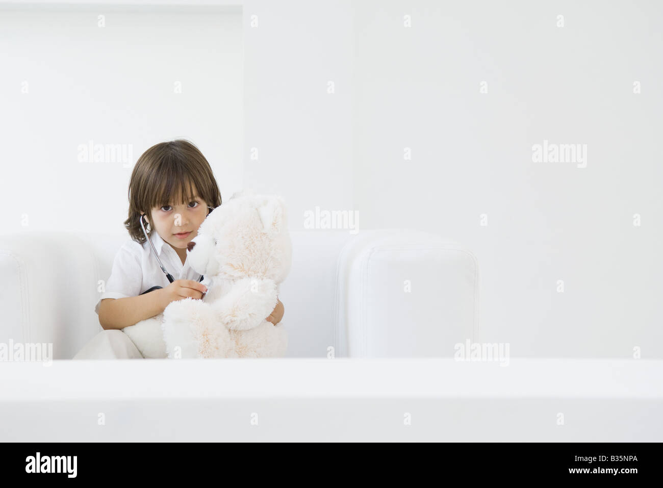 Little boy playing doctor with teddy bear, using stethoscope - Stock Image