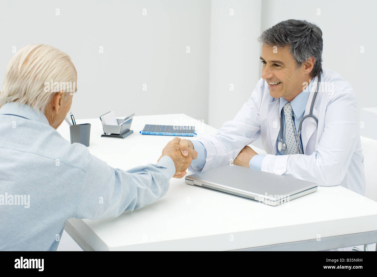 Doctor shaking hands with patient - Stock Image