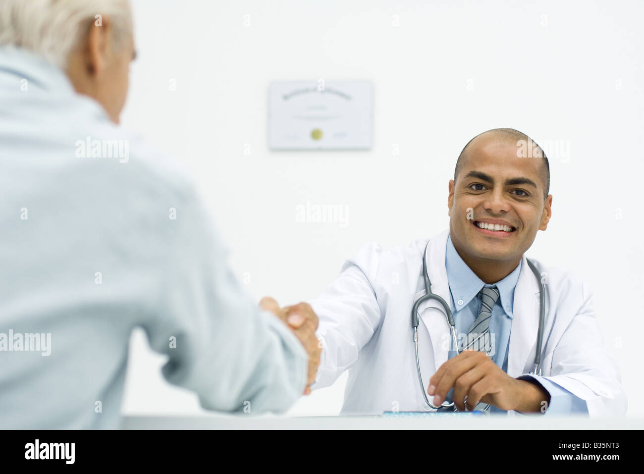 Doctor shaking hands with patient, smiling at camera, cropped - Stock Image