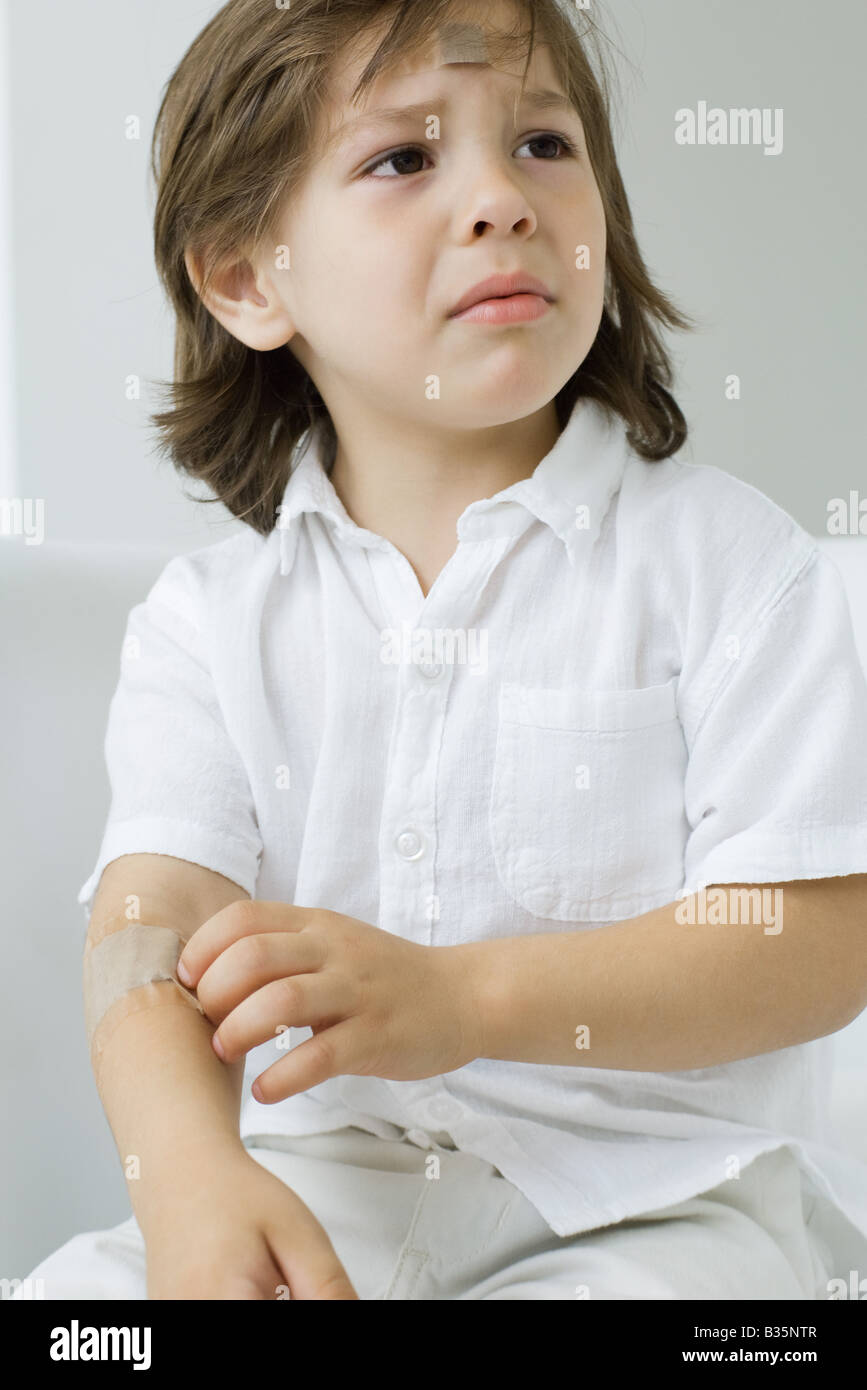 Little boy picking at adhesive bandage on his arm, frowning Stock Photo