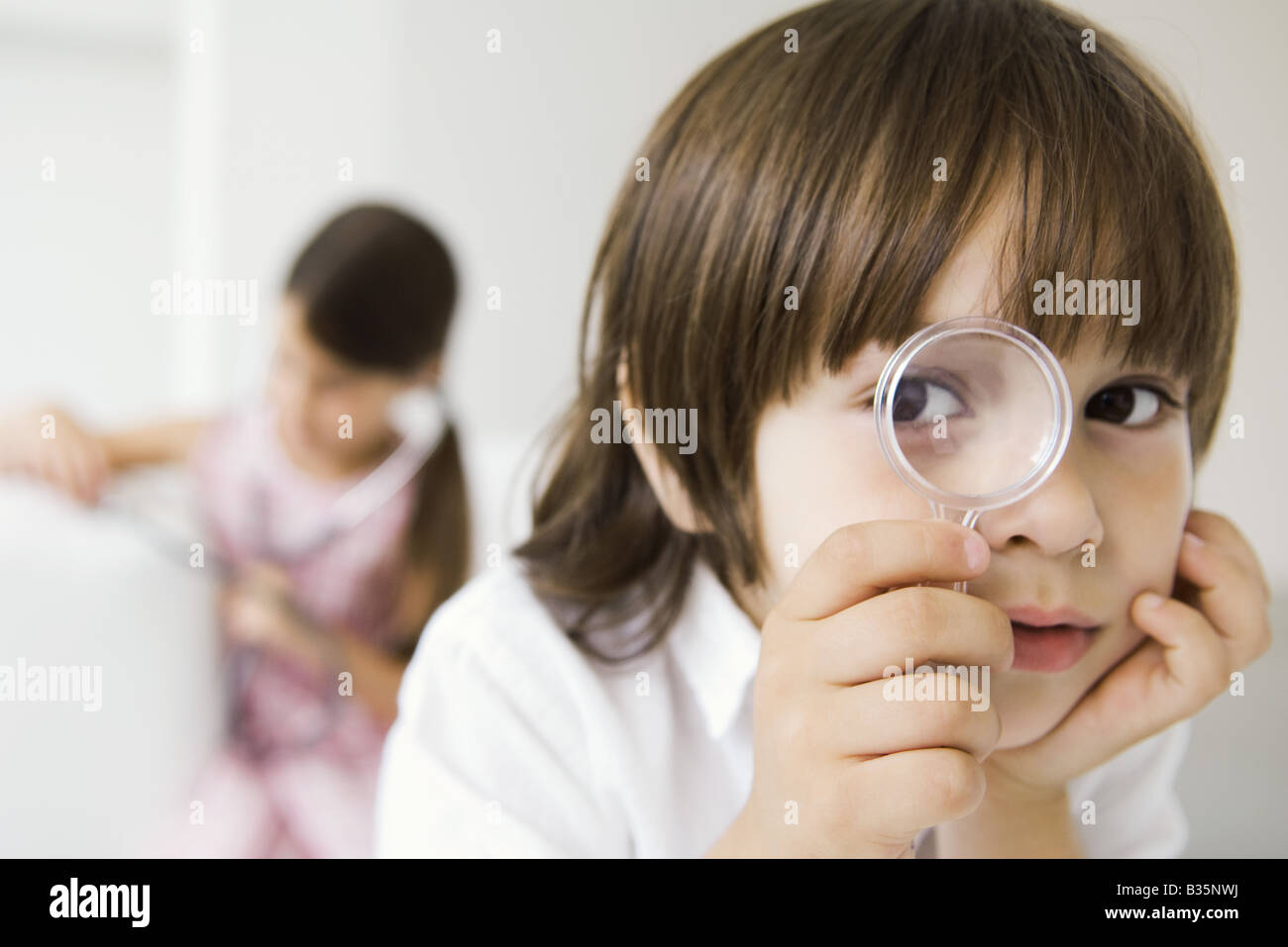 Little boy looking through magnifying glass at camera - Stock Image