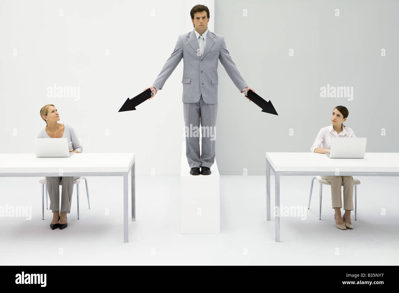Businessman standing between two female employees, pointing arrows at each of them - Stock Image