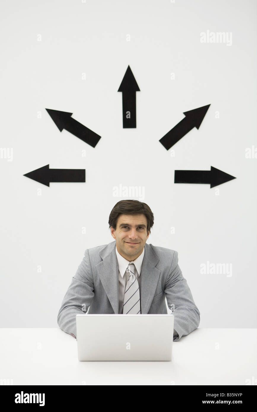 Businessman sitting with laptop, smiling, arrows pointing several directions above his head - Stock Image