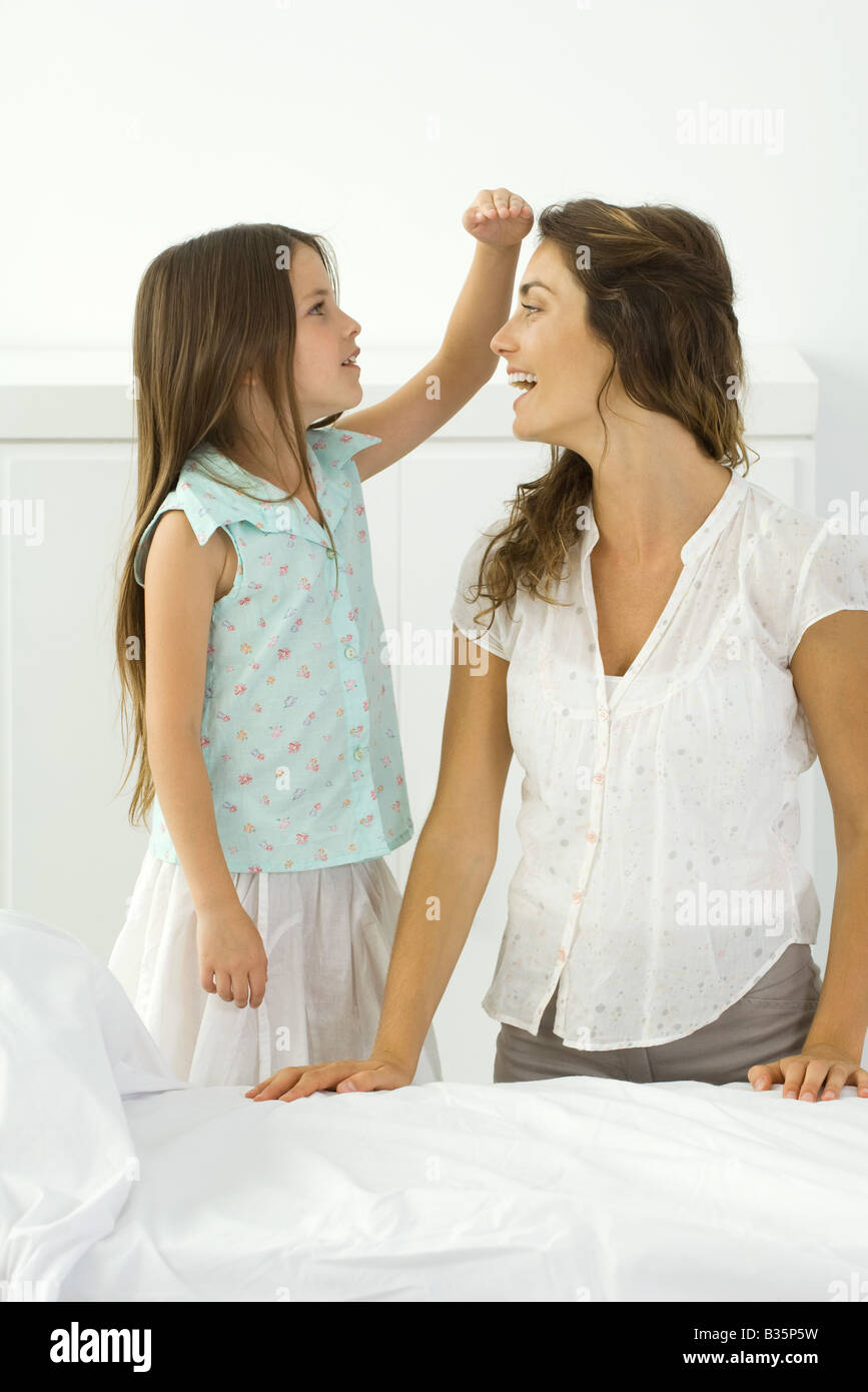 Little girl standing beside kneeling mother, comparing height with her hand - Stock Image
