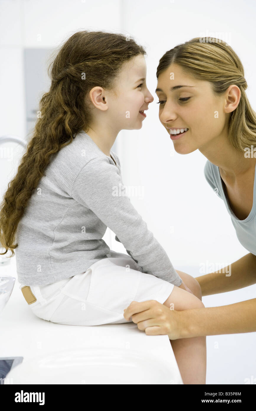 Little girl whispering in her mother's ear, side view - Stock Image