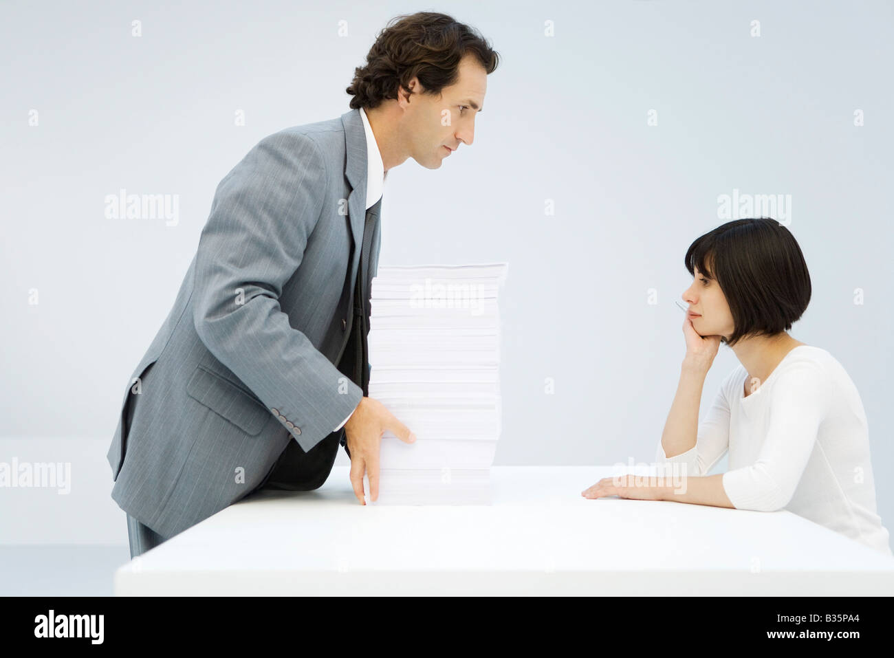 Businessman sliding tall stack of paper across a table to woman leaning on her elbow - Stock Image
