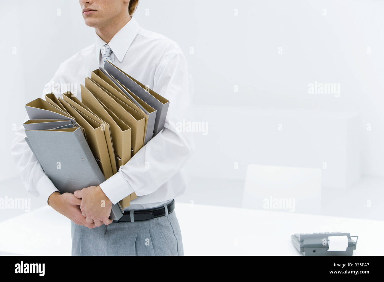 Office worker carrying many binders, cropped view - Stock Image