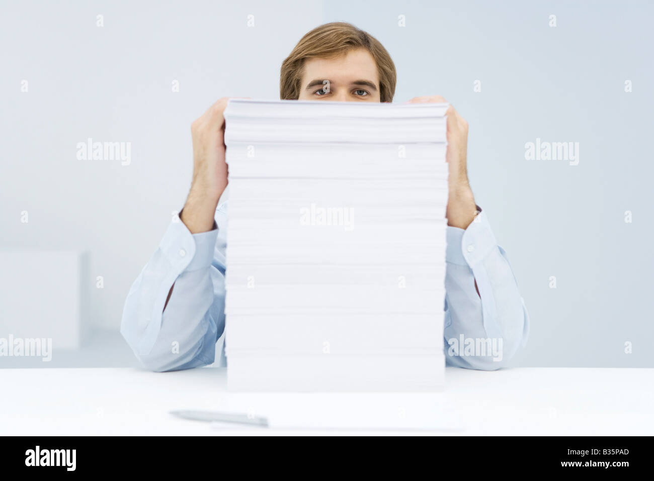 Man peering over tall stack of paper - Stock Image