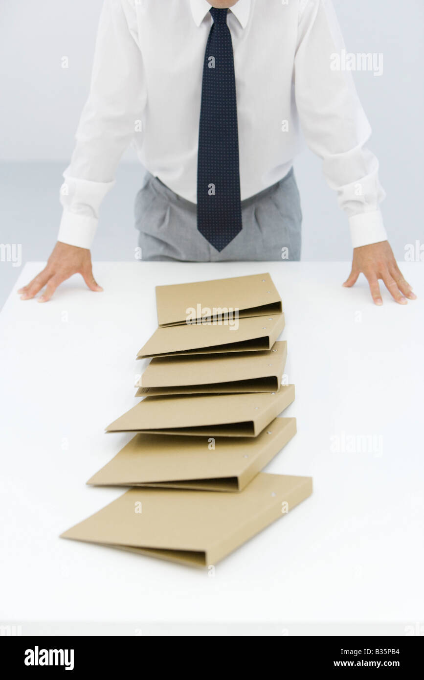 Binders lying on table after a chain reaction of being pushed over, cropped view of businessman - Stock Image