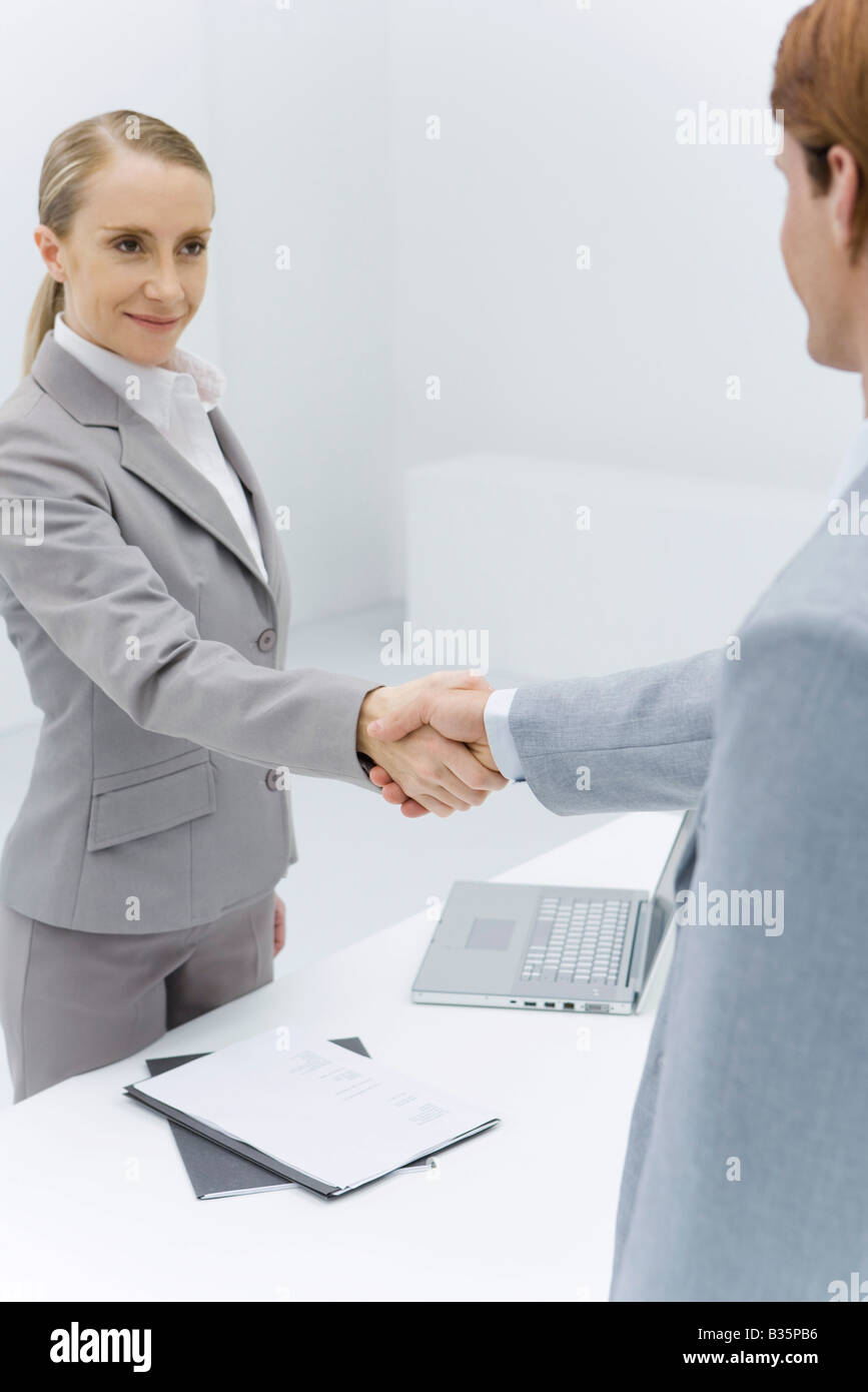 Businesswoman shaking hands with cropped view of red-headed businessman - Stock Image