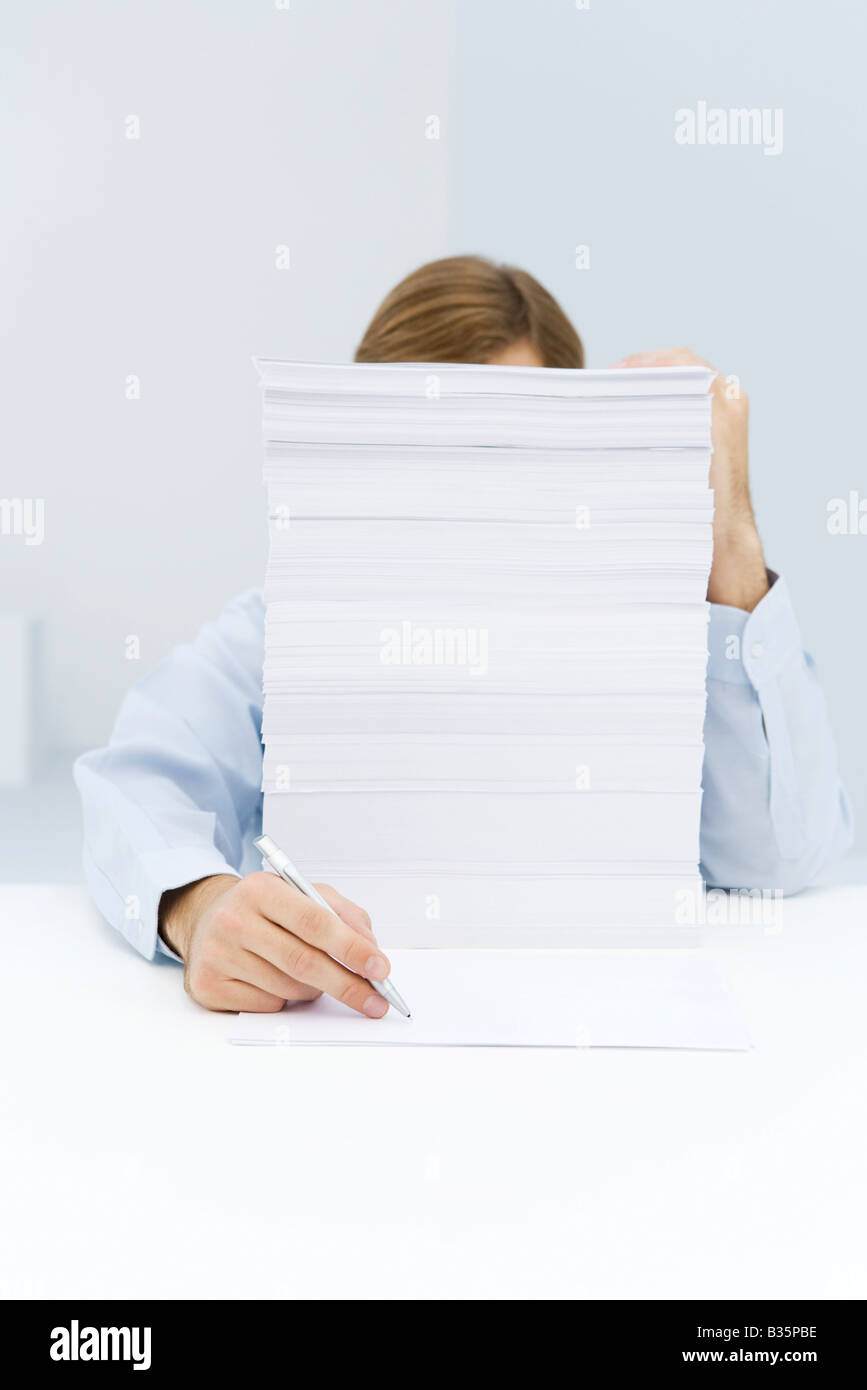 Man hiding behind tall stack of paper, reaching around to write on a single sheet of paper - Stock Image