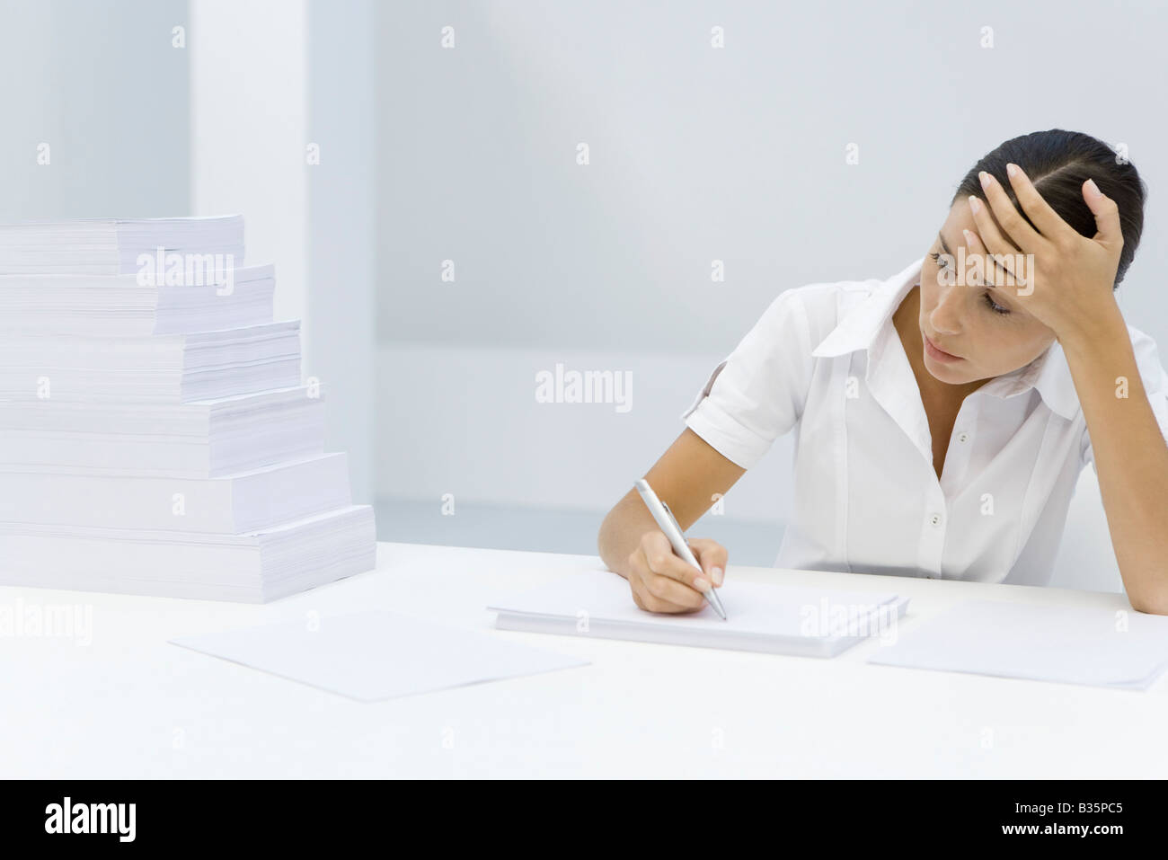 Woman holding her forehead, writing on blank sheet of paper, looking at staggered pile of paper - Stock Image