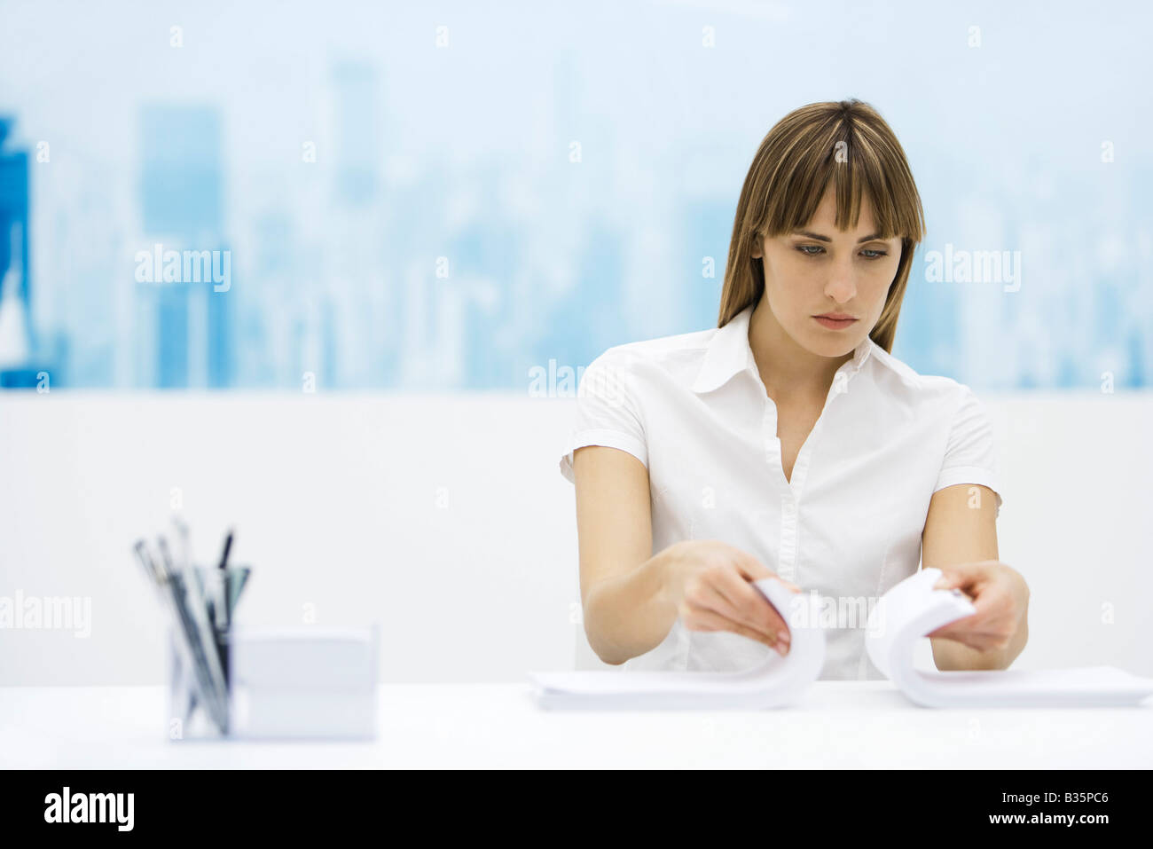 Woman shuffling two stacks of paper together, sitting at desk - Stock Image