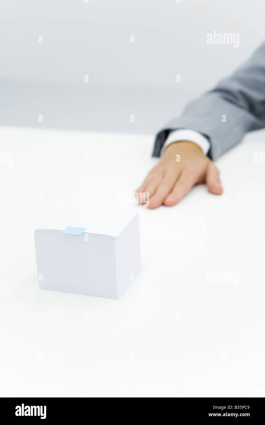 Stack of paper with small adhesive note stuck on it, cropped view of arm nearby - Stock Image