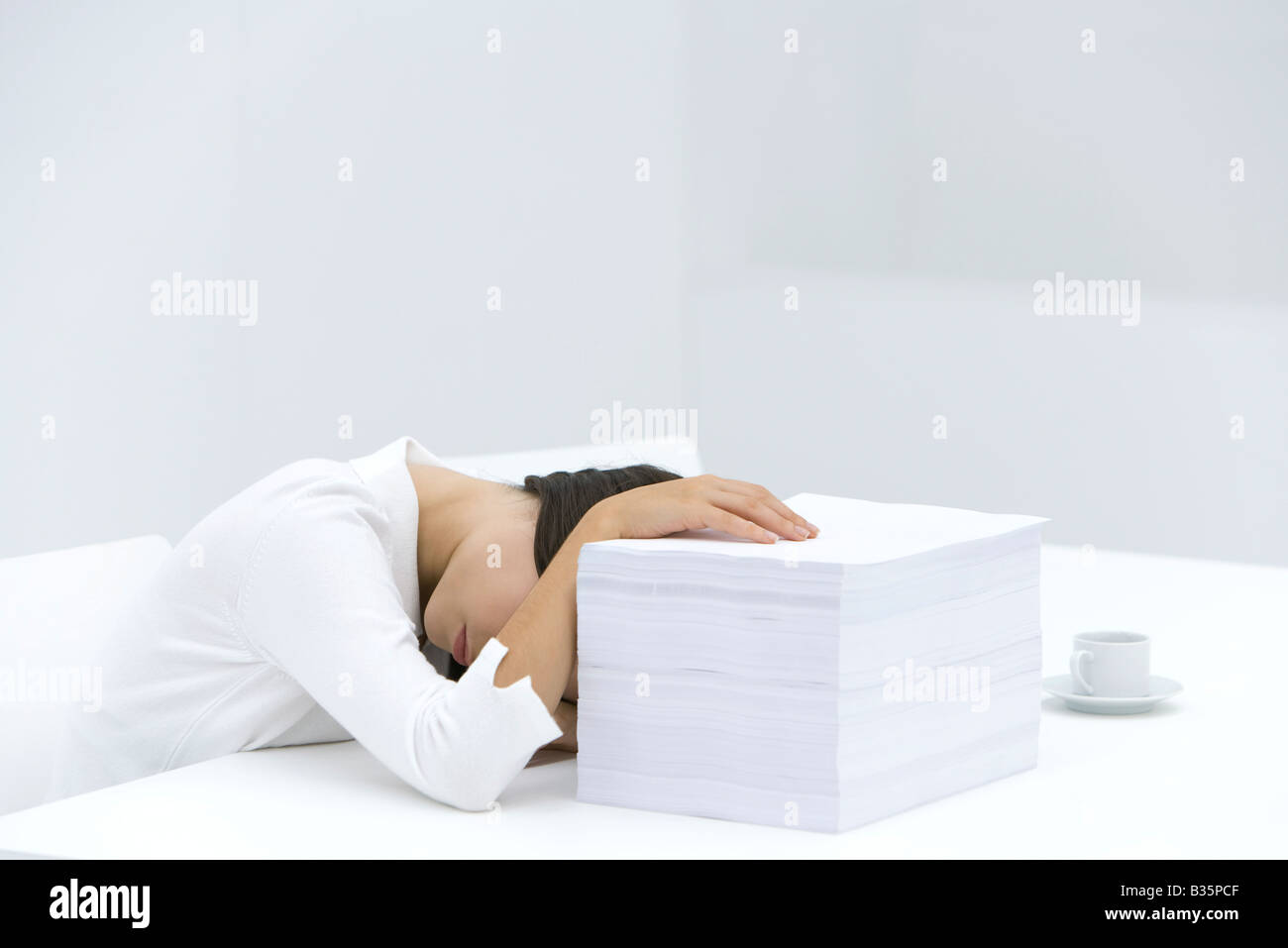 Woman with head down on desk, arm obscuring face, hand on top of stack of paper - Stock Image
