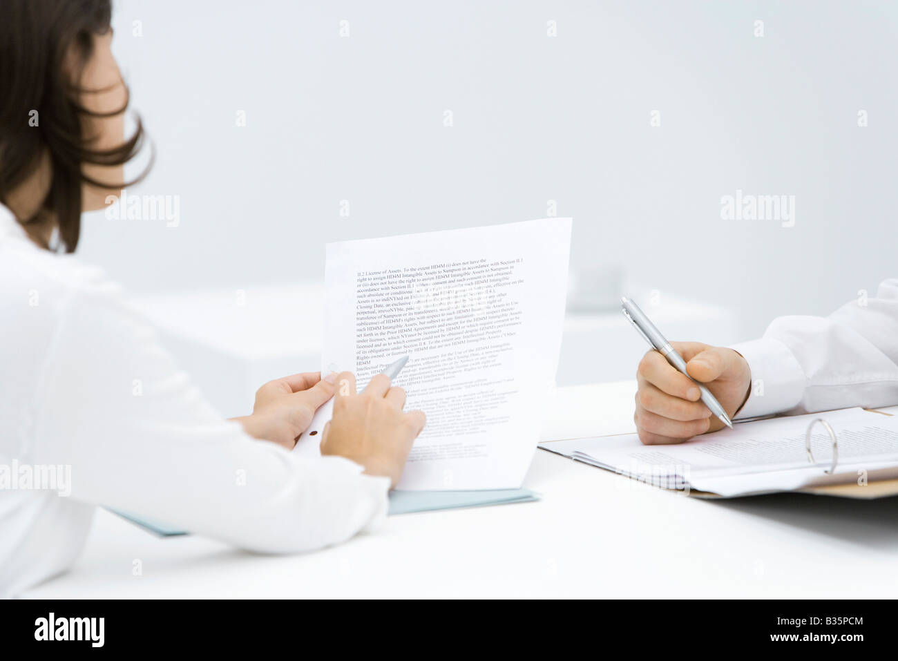 Woman scrutinizing contract, man editing document in binder, cropped view - Stock Image