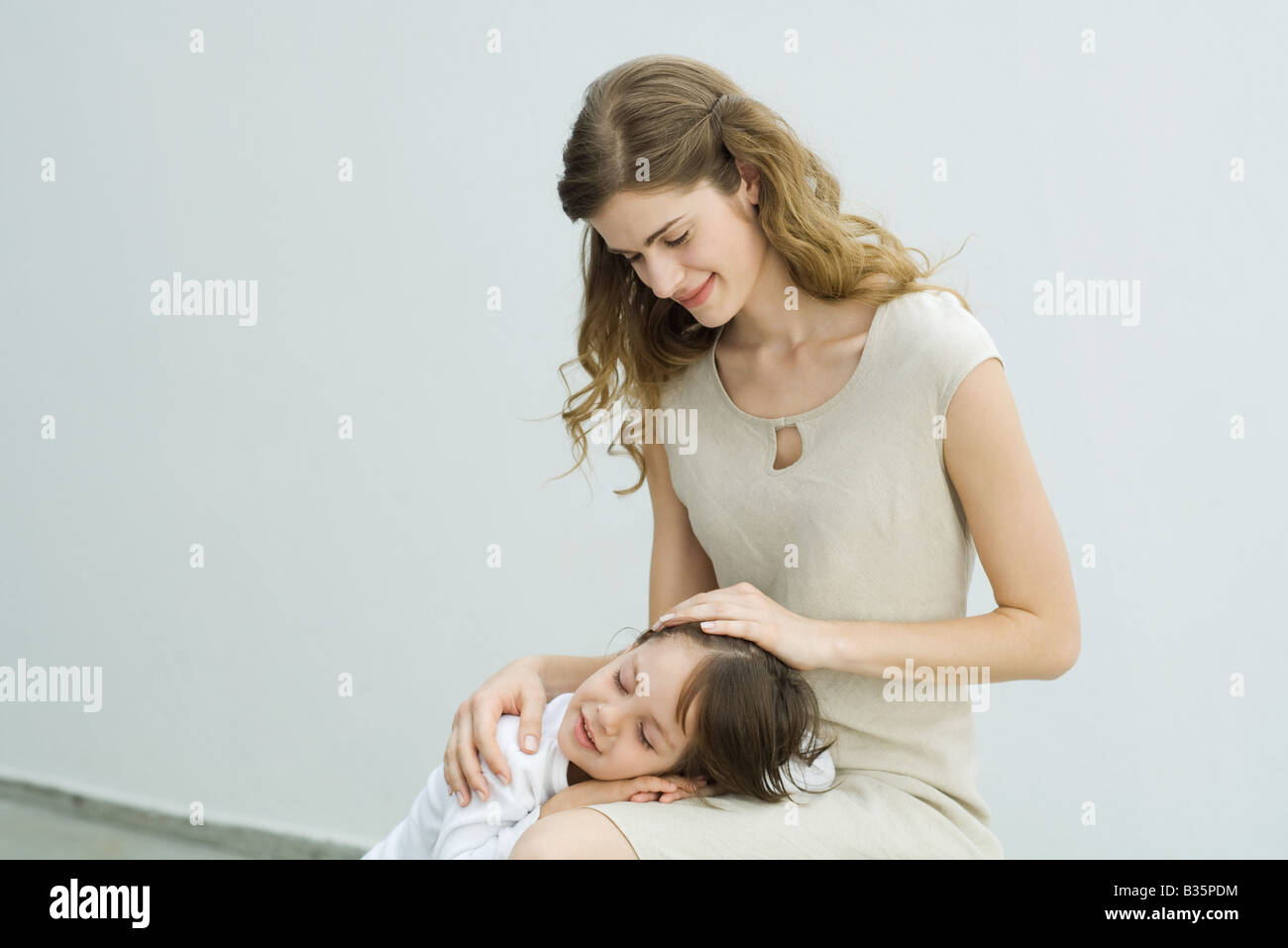 Little boy resting head on mother's lap, woman stroking child's hair - Stock Image