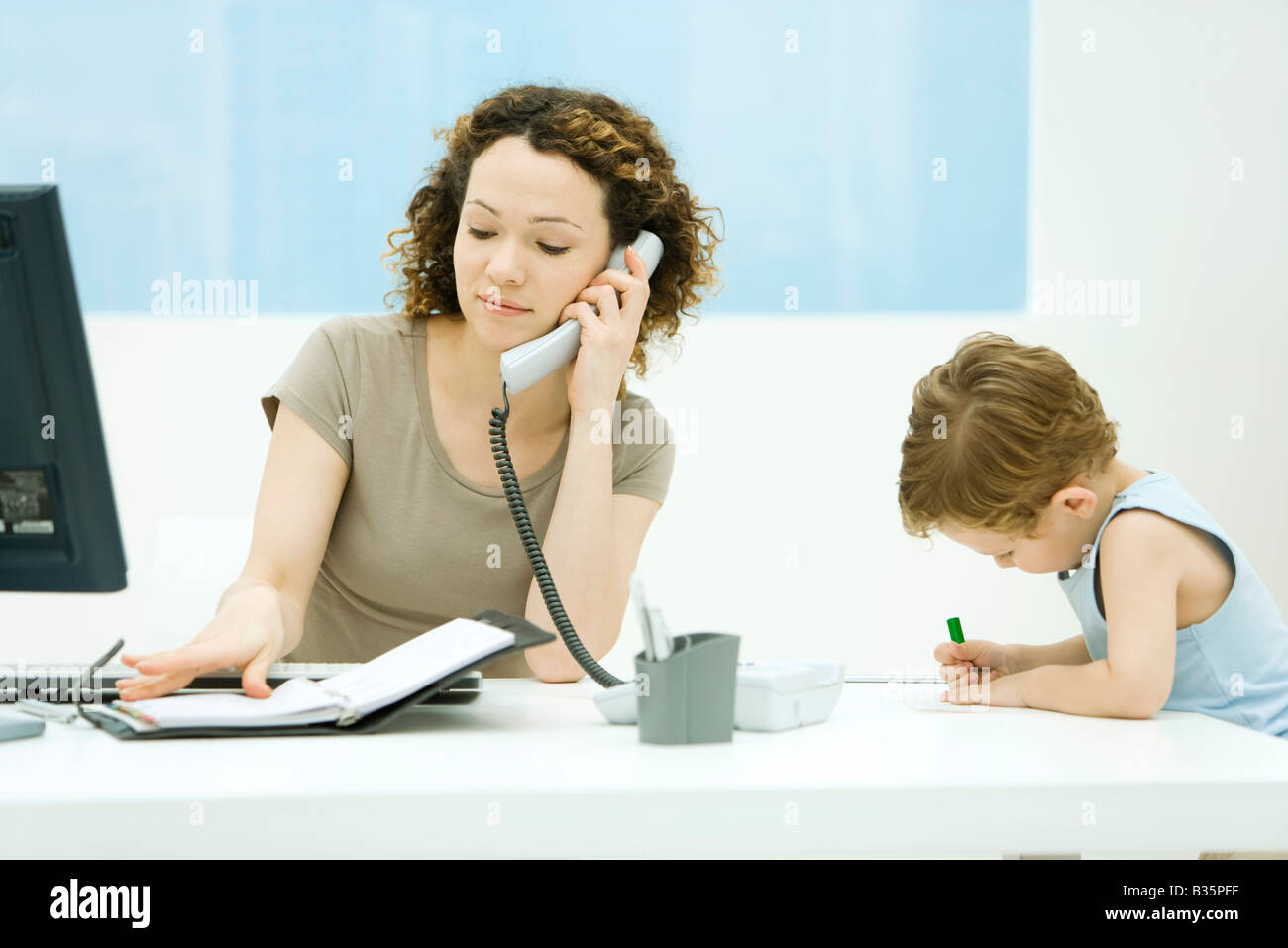 Woman using phone and looking at agenda, young son sitting beside her, coloring - Stock Image
