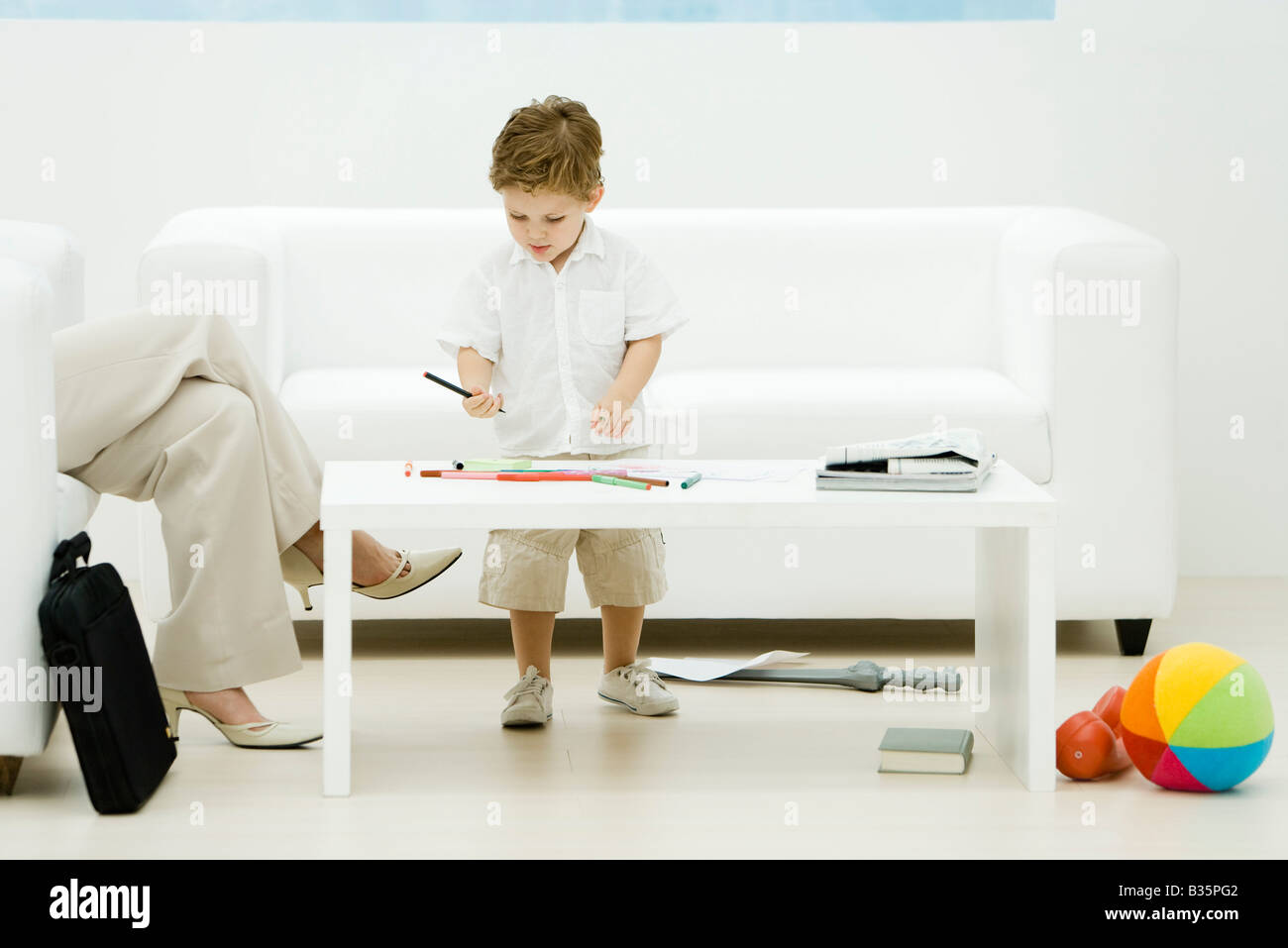 Professional woman and son in waiting room, boy coloring, cropped view - Stock Image