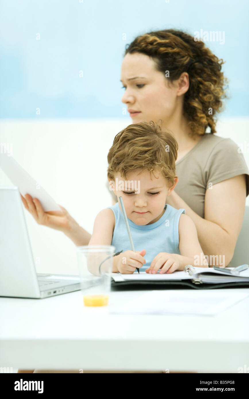 Mother holding son on lap, sitting in front of laptop, frowning at document - Stock Image