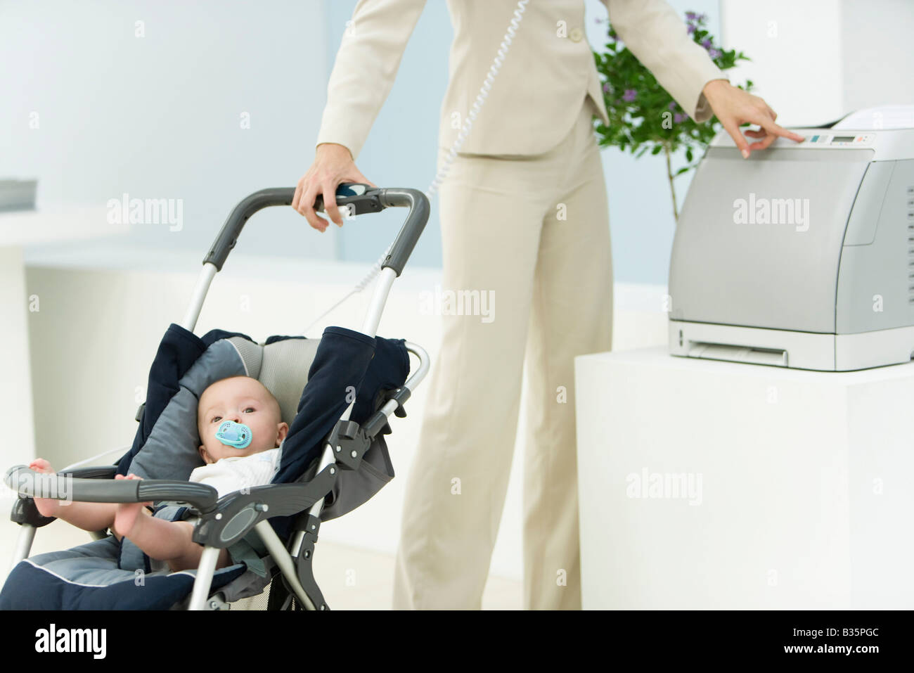 Professional woman in office with baby in stroller, using printer, cropped view - Stock Image