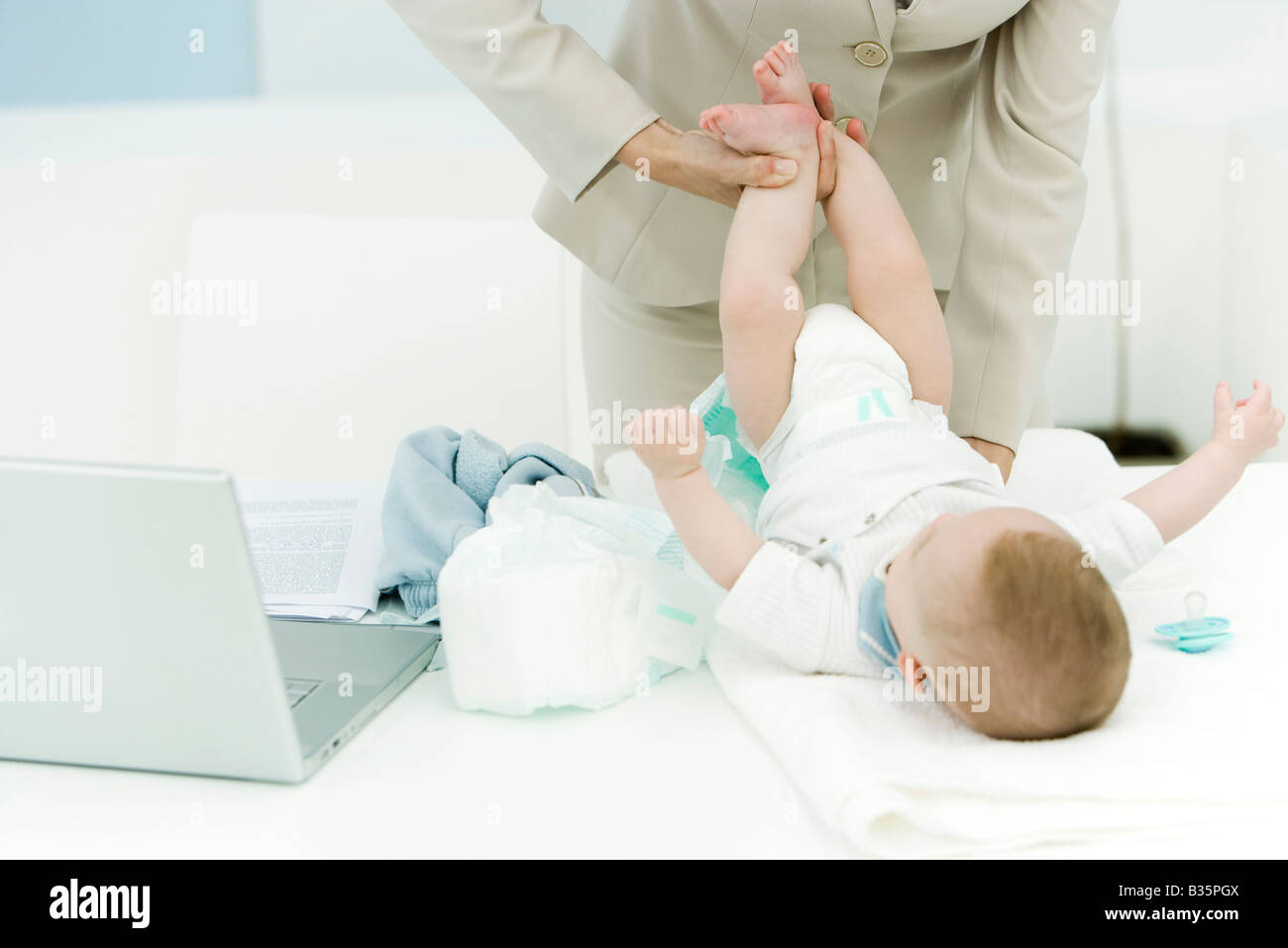 Professional woman changing baby's diaper on desk, cropped view Stock Photo