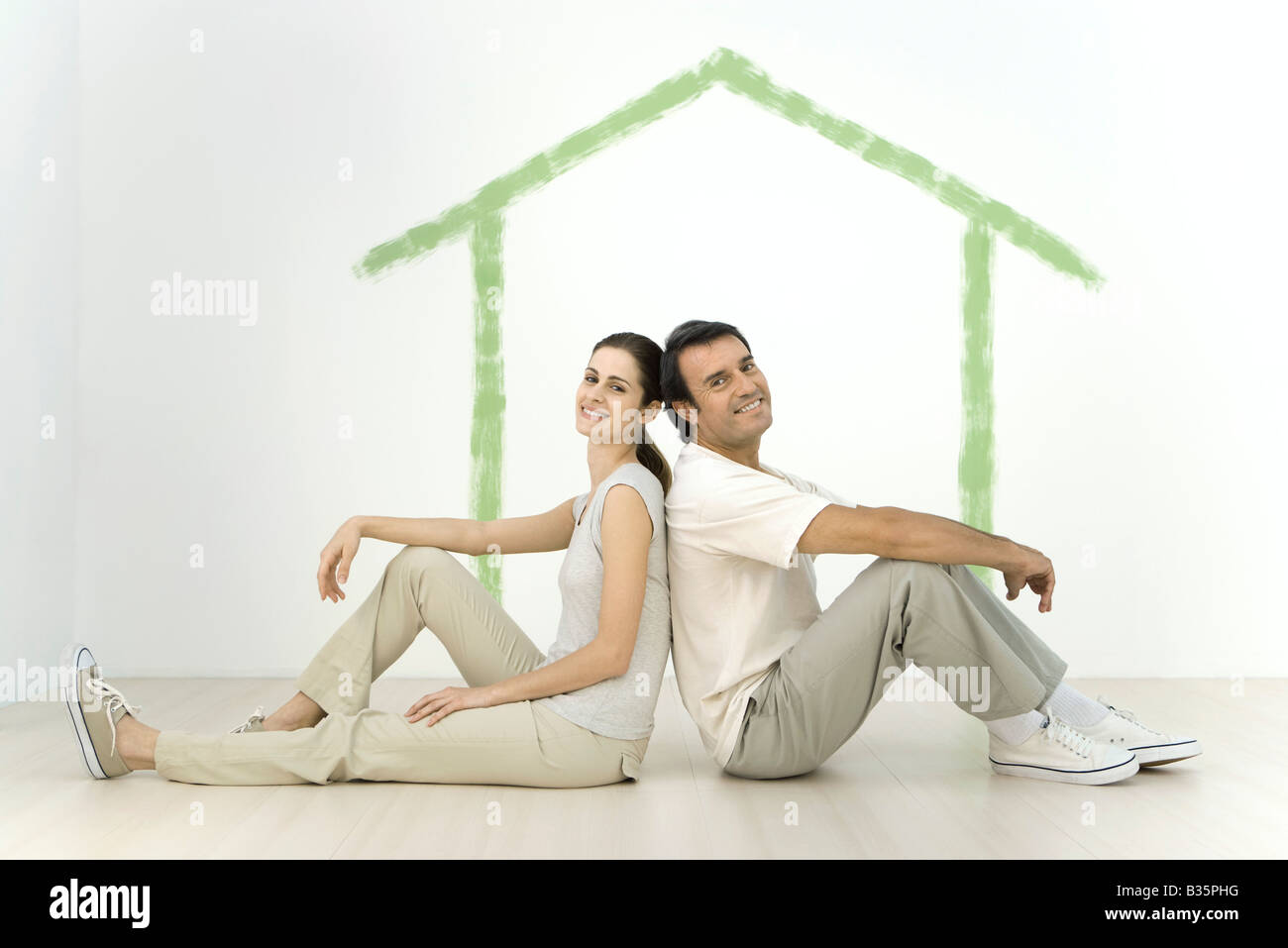 Couple Sitting Back To In Front Of An Outline A House Painted On Wall