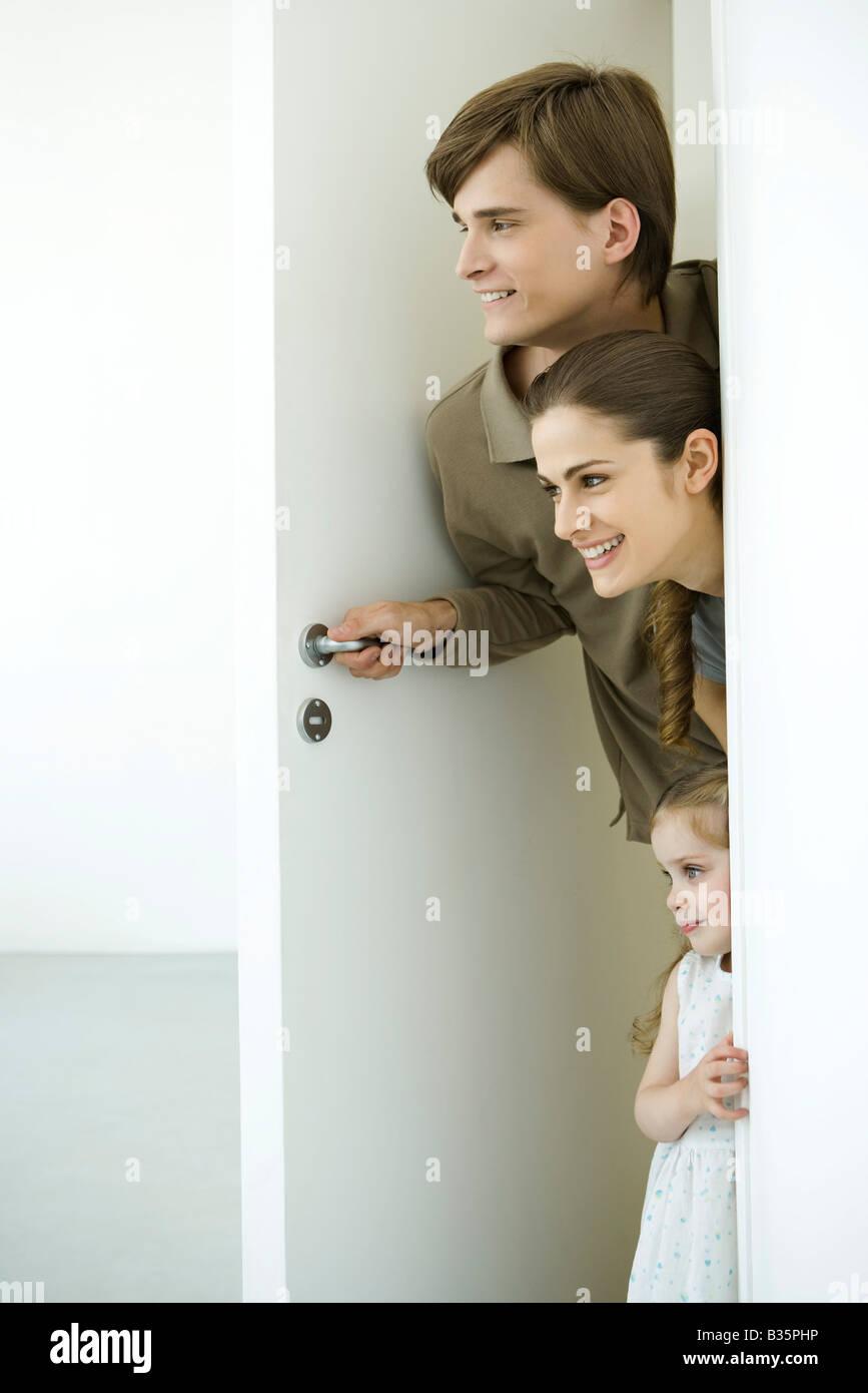 Family peeking in doorway - Stock Image