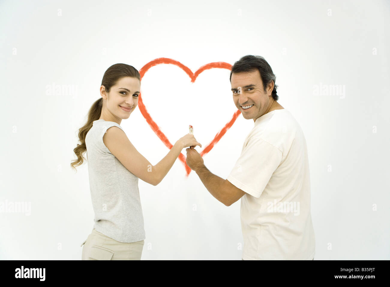 Couple standing in front of heart painted on wall, both holding onto the same paintbrush - Stock Image