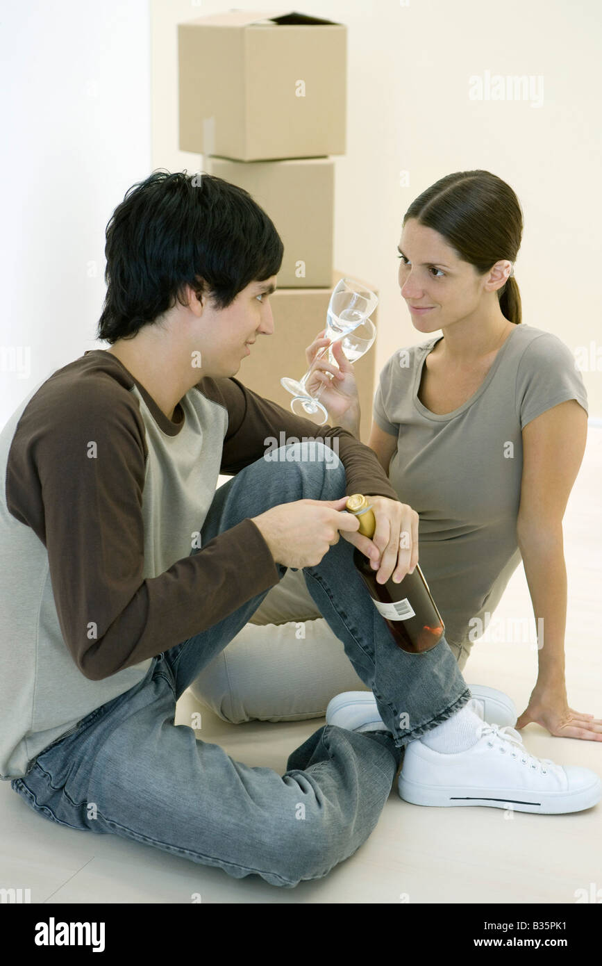 Couple sitting on the floor together, woman holding pair of wine glasses, man opening wine bottle - Stock Image