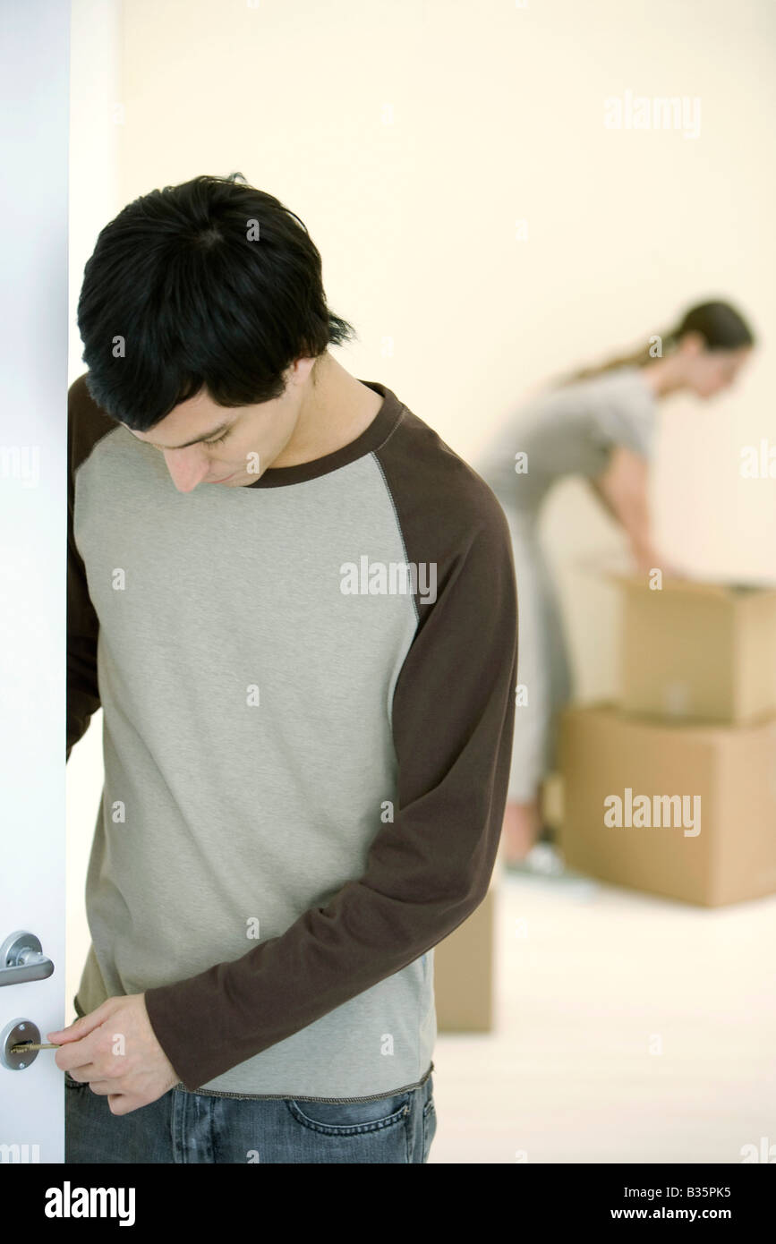 Man testing key on door lock, woman unpacking boxes in background - Stock Image