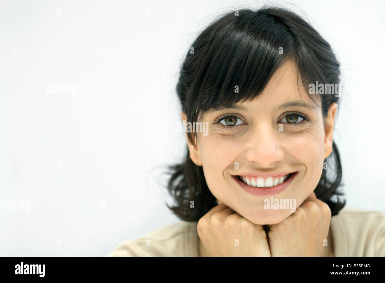 Woman smiling at camera, hands under chin, portrait - Stock Image