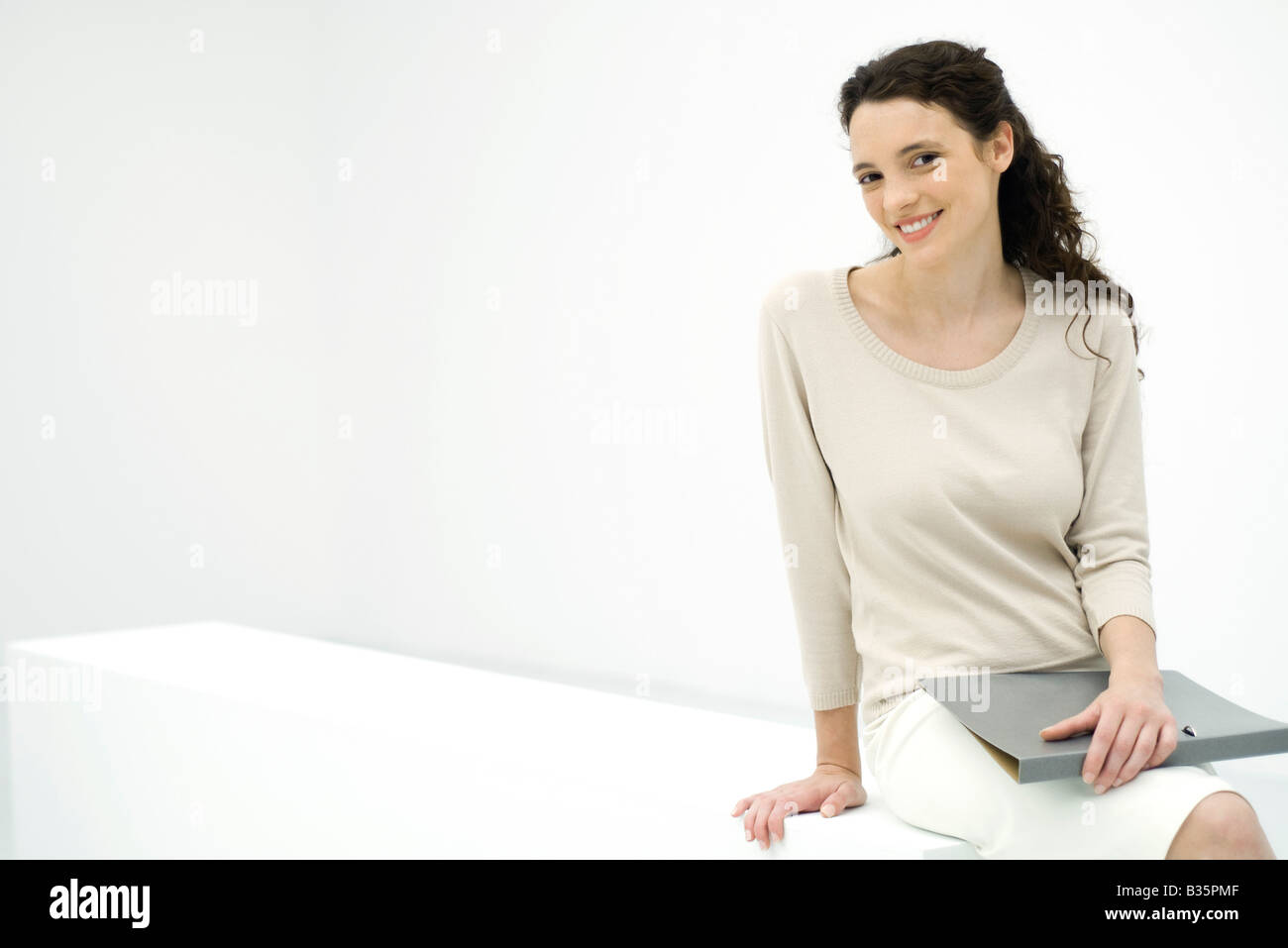 Young professional woman holding binder, smiling at camera - Stock Image
