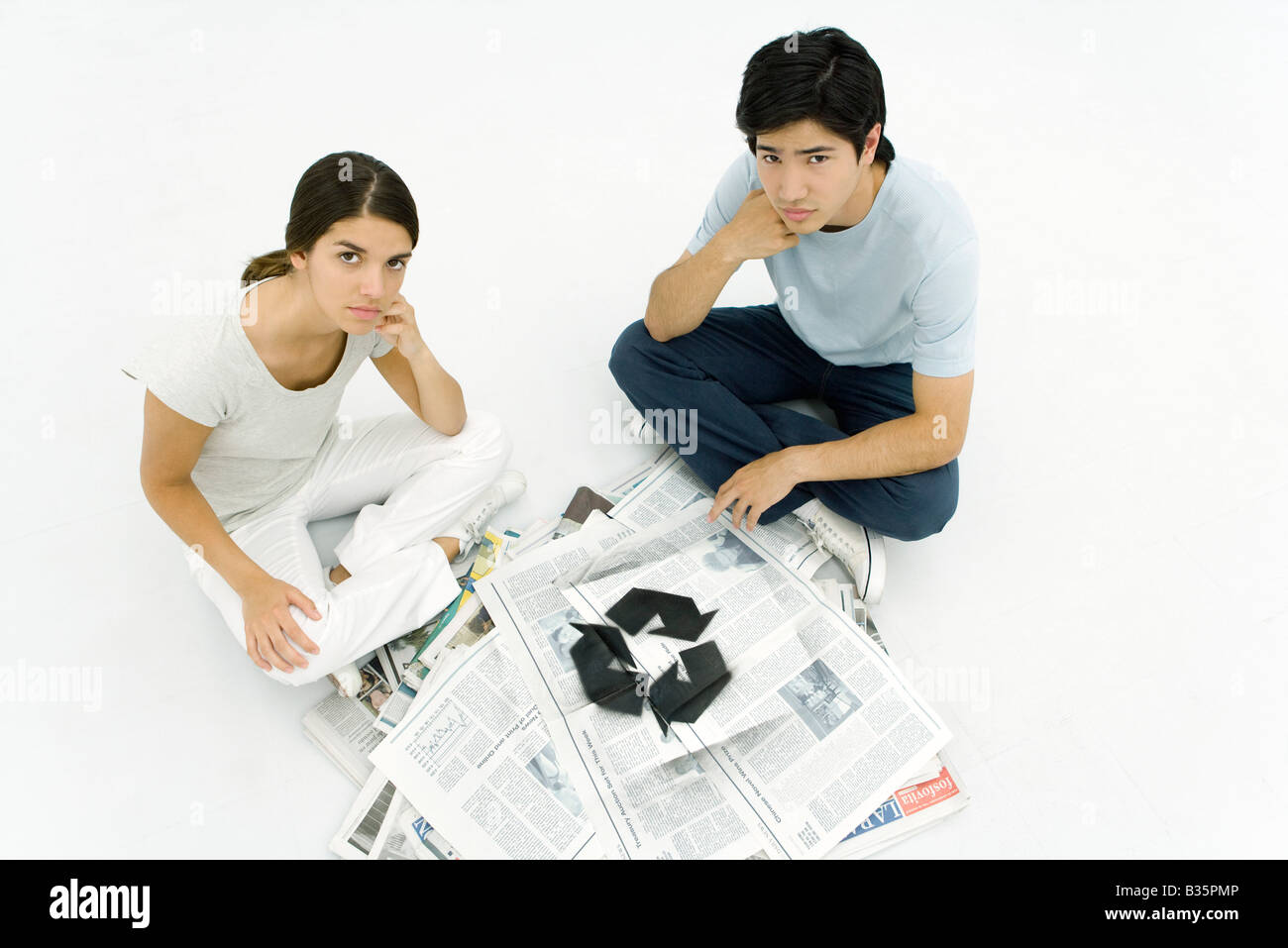 Young couple sitting beside stack of newspapers stenciled with recycling symbol, looking up at camera - Stock Image