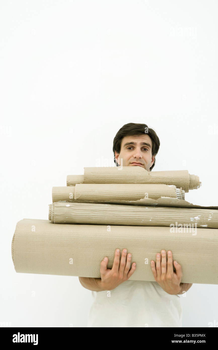 Man carrying stack of corrugated cardboard, looking at camera - Stock Image