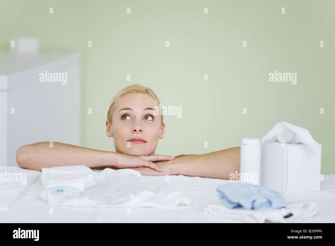 Woman in nursery, resting head on arms, looking up, smiling - Stock Image