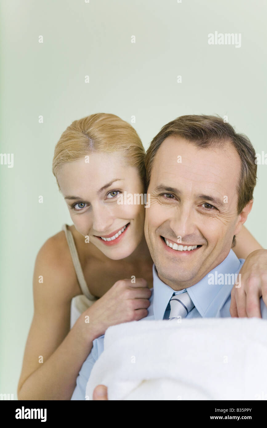 New parents smiling at camera, man holding wrapped up baby - Stock Image