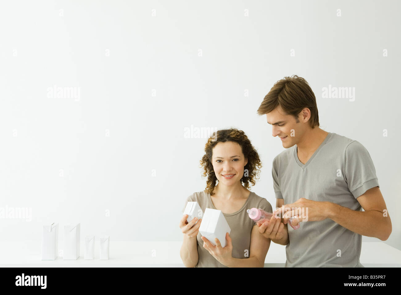 New parents looking at milk cartons, man holding baby bottle, woman smiling at camera - Stock Image