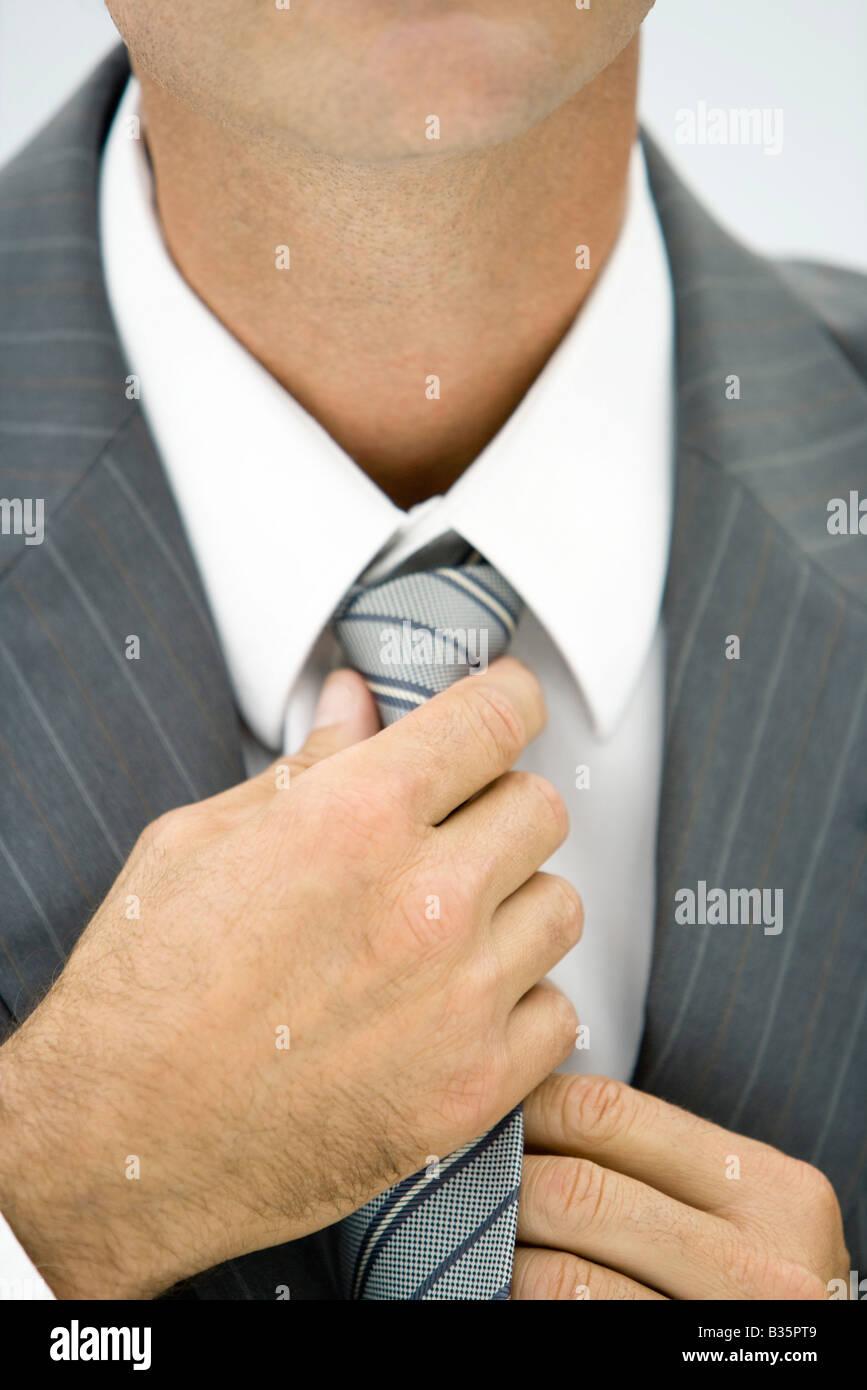 Businessman adjusting neck tie, close-up, cropped Stock Photo