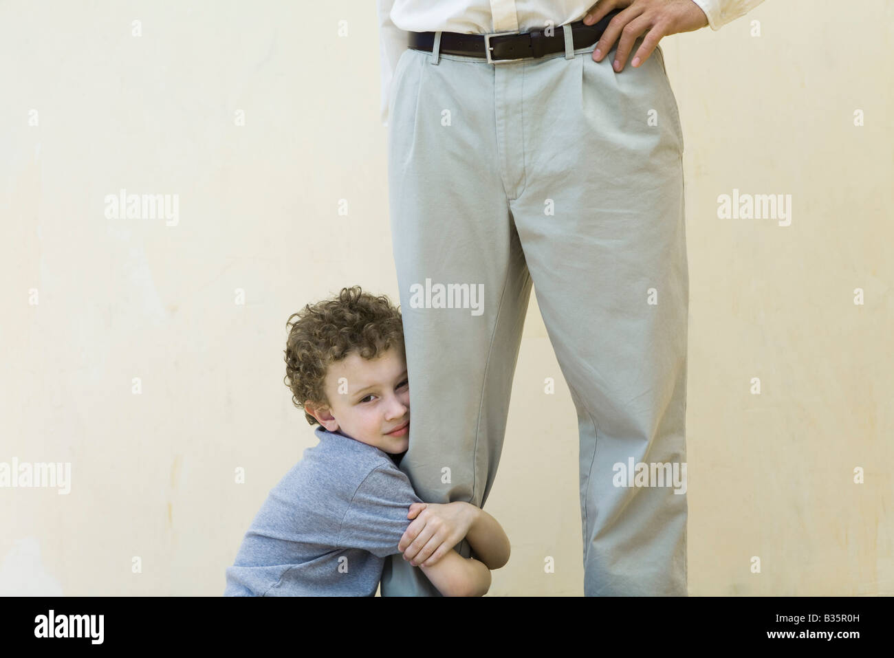 Boy clinging to his father's leg, looking at camera, cropped view - Stock Image