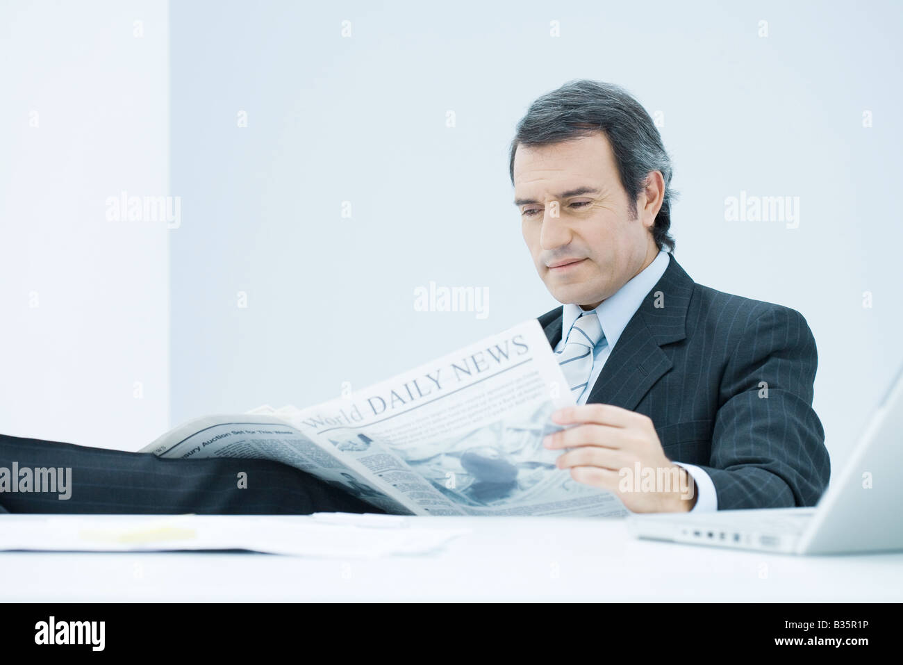 Businessman sitting at desk, reading newspaper, looking down with concerned expression - Stock Image