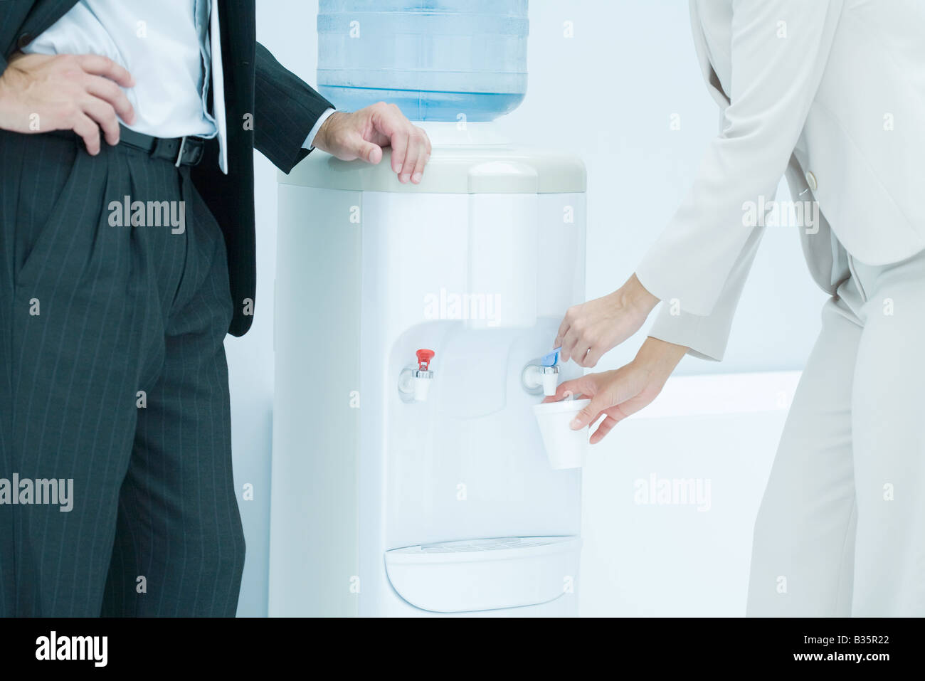 Professional woman filling disposable cup with water from water cooler, male colleague standing nearby, cropped - Stock Image