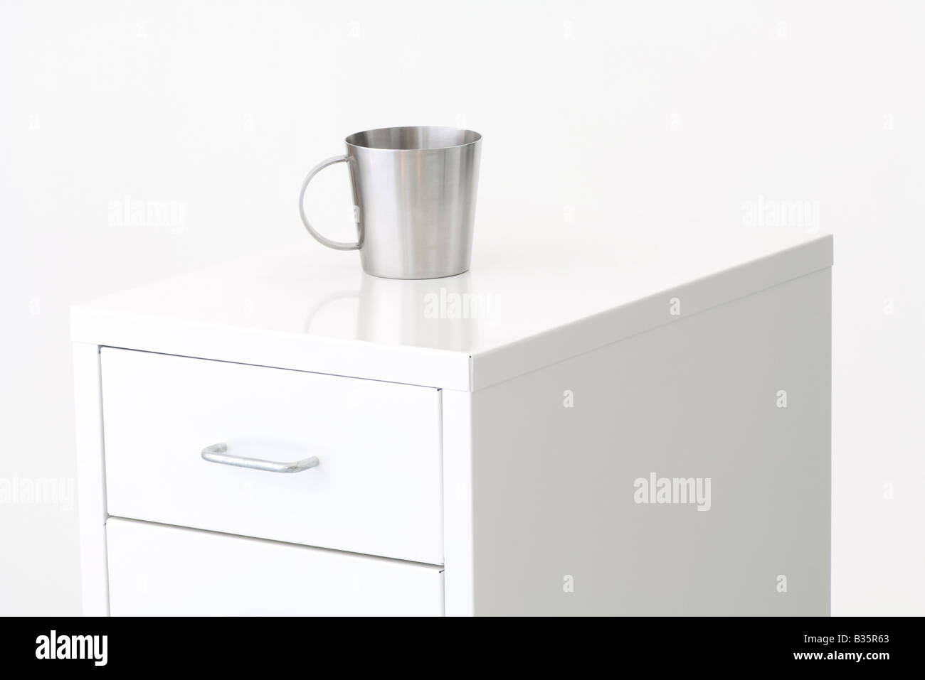 Metal cup on top of a filing cabinet - Stock Image