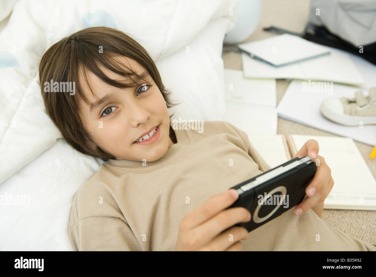 Boy holding handheld video game, lying down and smiling at camera - Stock Image