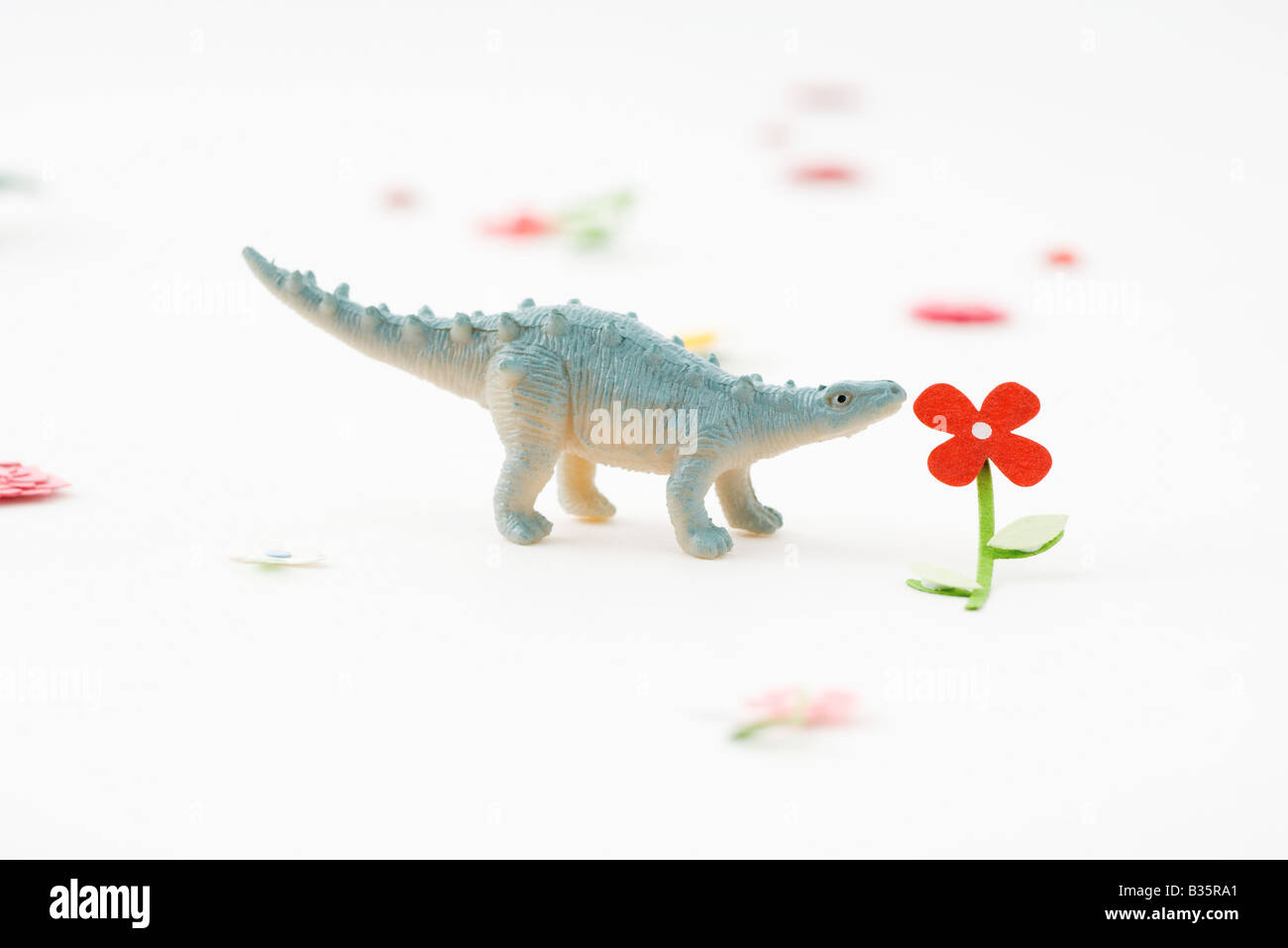 Toy dinosaur smelling artificial flower - Stock Image