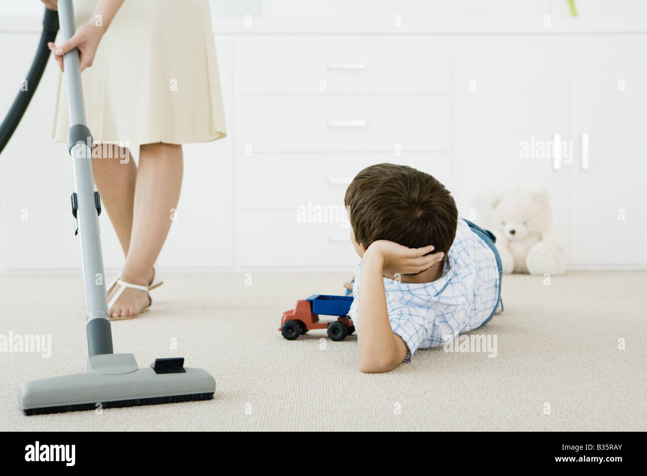 Boy lying on the ground with toys, looking up at his mother vacuuming around him - Stock Image